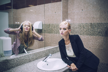 Beautiful woman businesswoman in front of a mirror with a reflec