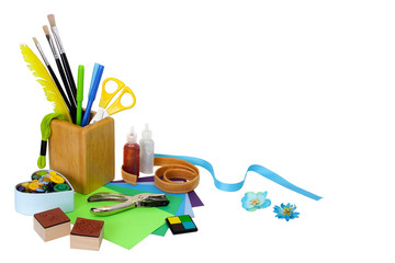 Assorted scrapbooking or card making supplies, isolated on white background with soft shadows. Copy space provided.