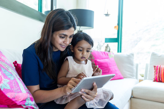Litlle girl play tablet pc with her mother at home