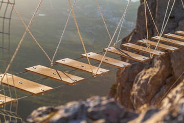 Two rope ladders  over abyss leading to catholic cross standing on top of montain