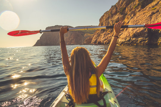 Young woman kayaking and holding oar over head