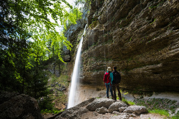 Two people standing by Pericnik Waterfall, Slovenia