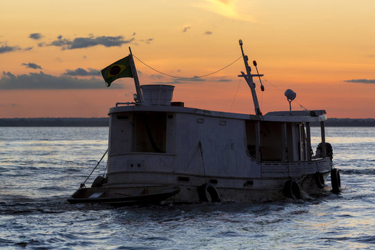 Silhouette of Amazon wooden boat on Rio Negro in Manaus, Brazil