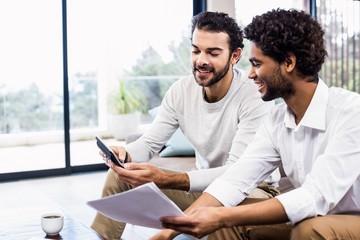 Smiling gay couple paying bills