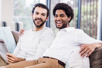 Happy gay couple reading newspaper