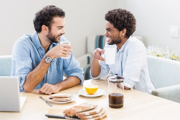 Happy gay couple having breakfast and talking