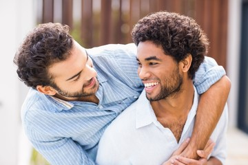 Smiling gay couple embracing each other