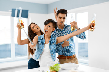 Party Home. Happy Friends Taking Selfie Photo With Smartphone Selfie Stick. People Eating Pizza, Drinking Beer And Celebrating Holiday Indoors. Friendship, Leisure, Technology Concept. Celebration.