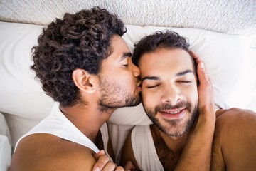 Close up of man kissing his partner while lying on bed at home