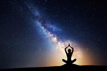 Milky Way and silhouette of a woman practicing yoga.