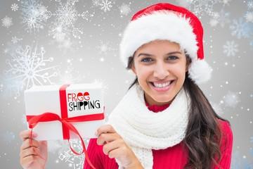 Composite image of festive brunette holding gift