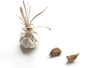 Heads of young and mature garlic, and raw cloves of garlic isolated on a white background.