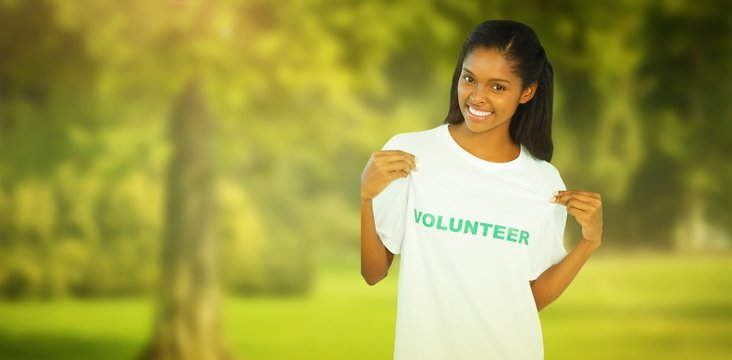 Young woman wearing volunteer tshirt and showing sign