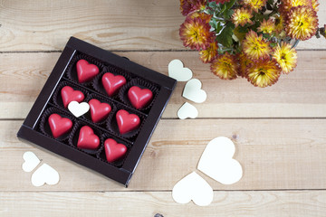 Red chocolate hearts in box and flowers on wooden table