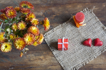 Valentine's Day gift, red chocolate hearts, candle and golden chrysanthemum on wooden background