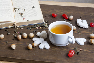 Cup of hot tea with books and flowers, cookies hearts, tea leaves, hazelnuts, candied fruit