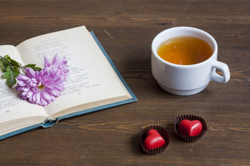 Cup of hot tea with books and flowers, red chocolate hearts