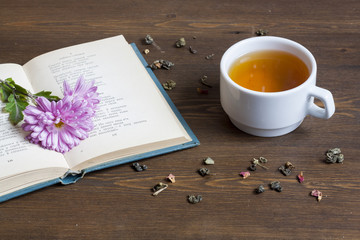 Cup of hot tea with books and flowers, tea leaves