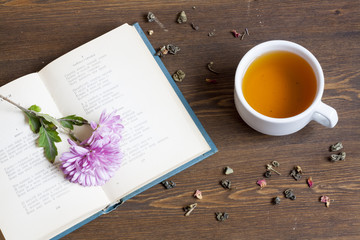 Cup of hot tea with books and flowers and tea leaves