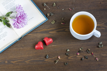 Cup of hot tea with books and flowers, red chocolate hearts and tea leaves