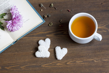 Cup of hot tea with books and flowers and cookies.