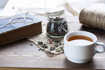 Cup of hot tea with books, tea leaves and flowers on wooden table. Vintage still life.