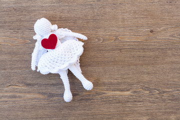 Valentines day crochet angel and heart on wooden table