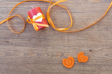 Valentines day crochet orange hearts, ribbon and candle on wooden table.