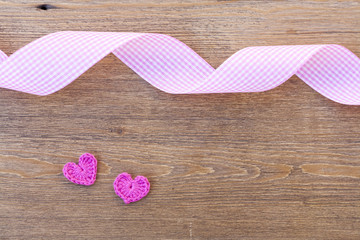 Valentines day crochet hearts and ribbon on wooden table