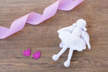 Valentines day crochet hearts and angel and ribbon on wooden table