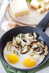 Scrambled eggs with mushrooms to frying pan, sliced cheese and herbs
