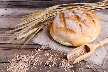 Homemade bread and ripe ears of wheat on a wooden background