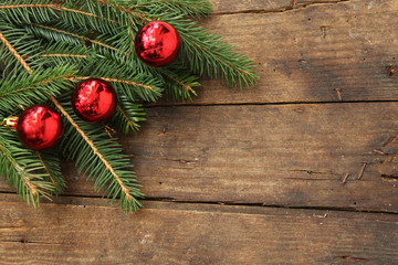 Christmas background - Christmas ornaments in bauble shape on fir tree - on wooden background