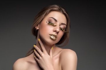 High fashion look, closeup beauty portrait of beautiful young woman model with bright makeup with perfect clean skin with colorful gold lips