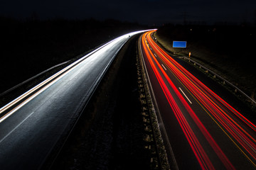 Car light trails with blue road sign, long exposure Wall mural