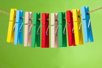wooden clothespin hanging on rope.  colorful clothespins.