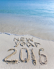 """On sand at ocean edge it is written """"2016"""".."""