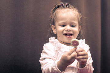 Beautiful little girl holding a small watermelon lollipop.