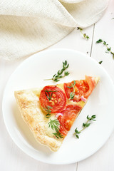 Piece of tomatoes pie on white plate