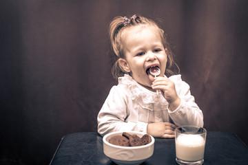 Cute little girl licking lollipop.