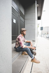 young handsome afro black man sitting on a staircase, smartphone
