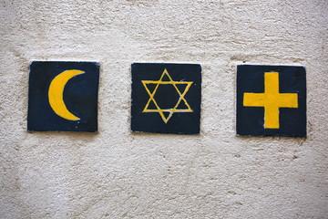 Set of 3 religious symbols: islamic crescent, jewish David's star, christian cross (wall sign on the street of Segovia, Spain)  Wall mural