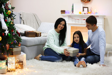 Happy family on the floor with gifts in the decorated Christmas room
