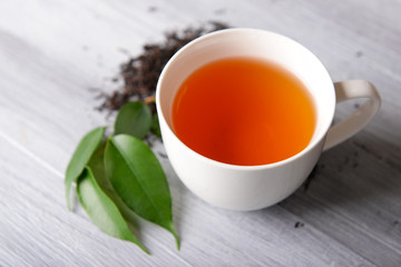 Ceramic cup of tea with scattered tea leaves around on light wooden background