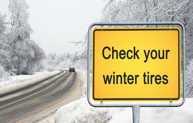 Check your winter tires - yellow traffic sign with text - snow on road and car in the background