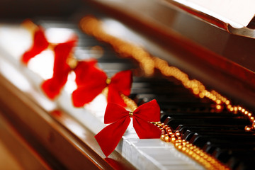 Piano keys decorated with golden Christmas decorations, close up