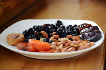 Dried fruits and almonds on the white plate