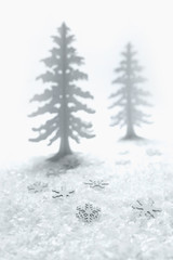 Wooden fir tree and snowflake table decorations on a bed of false snow.