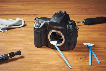 Digital photo camera with cleaning tools
