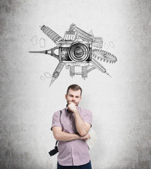 man with photo camera thinking about holidays